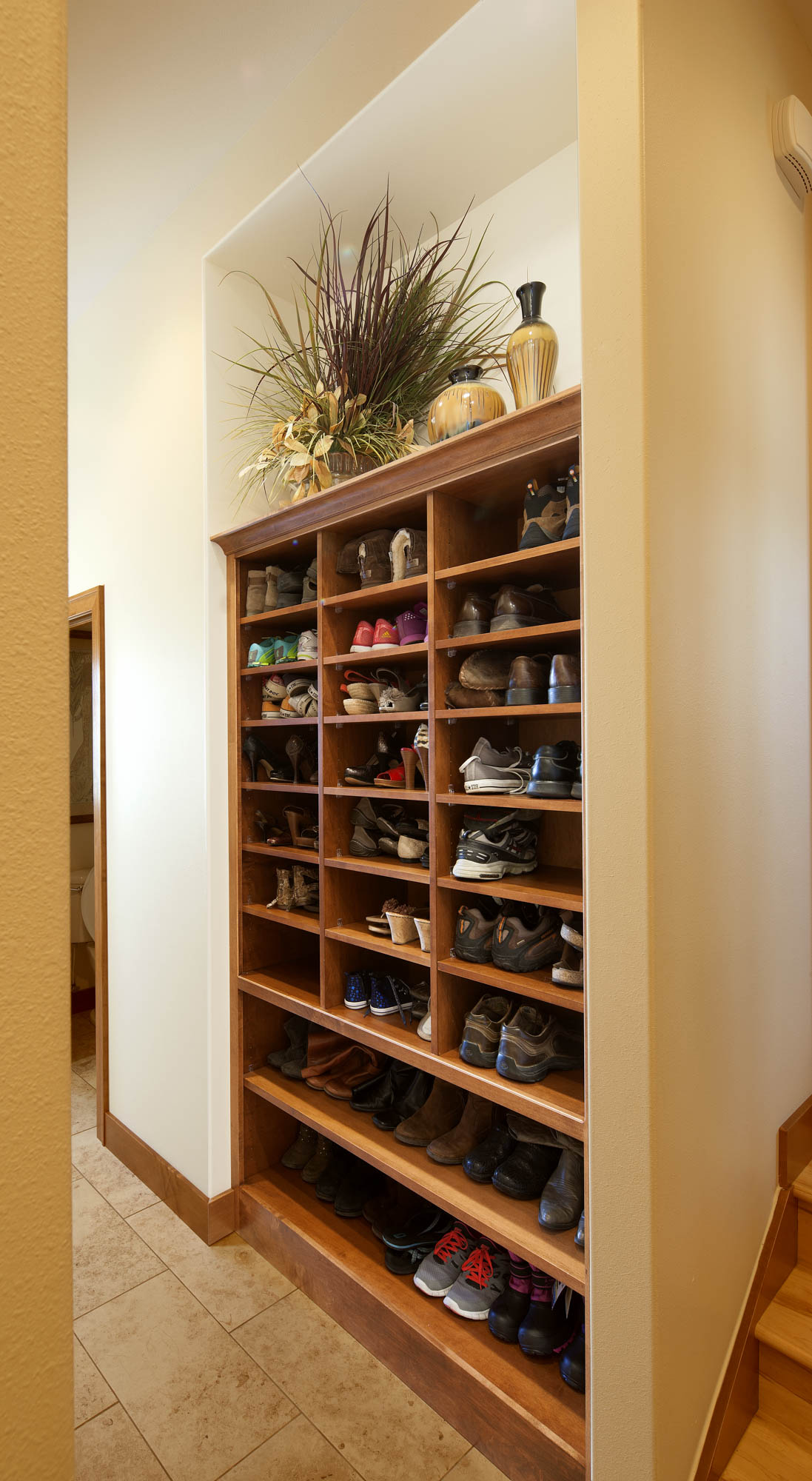 Stained mudroom shoe shelves in Autumn by Showplace Cabinetry