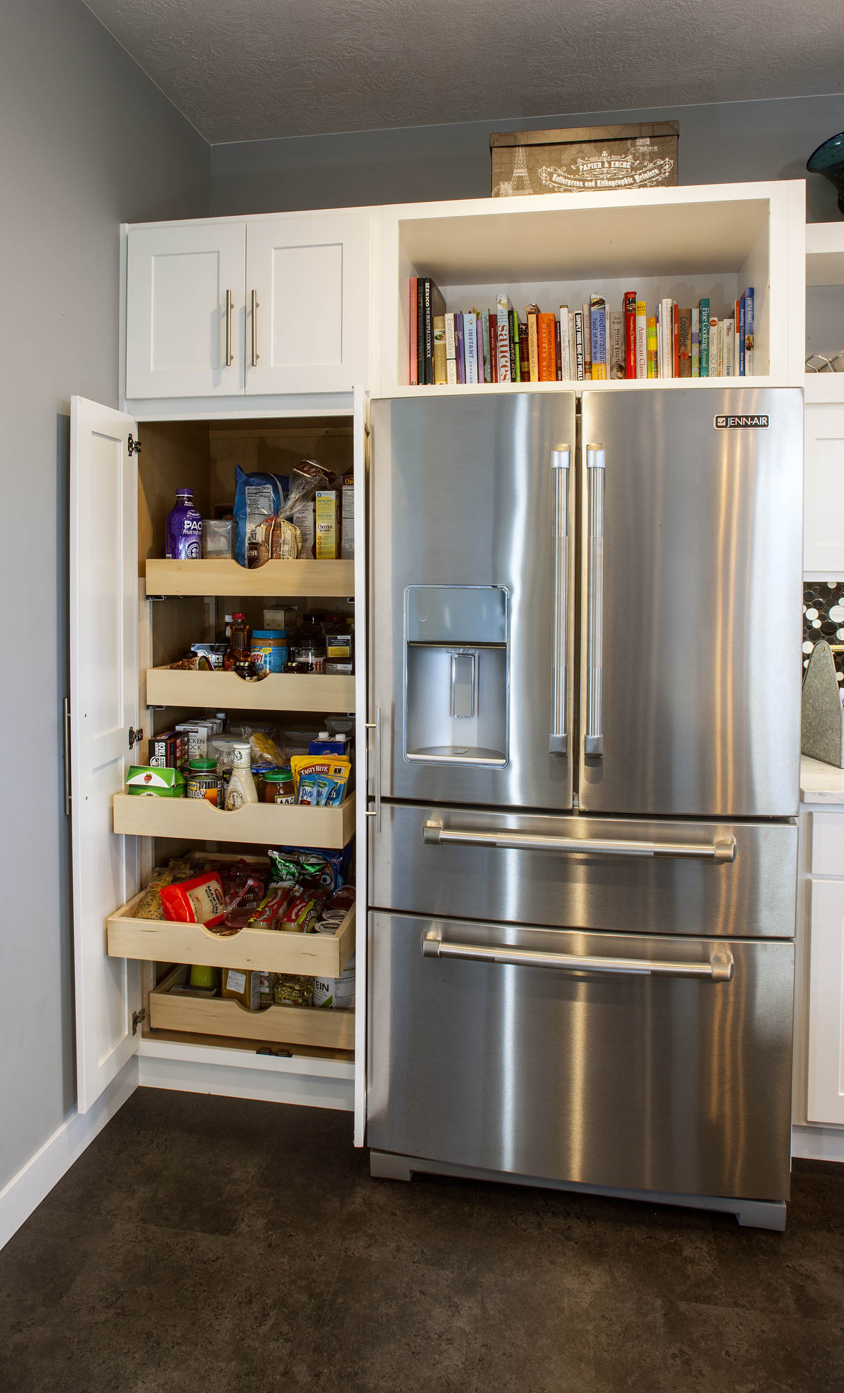 Painted kitchen cabinet with roll trays in White by Showplace Cabinetry