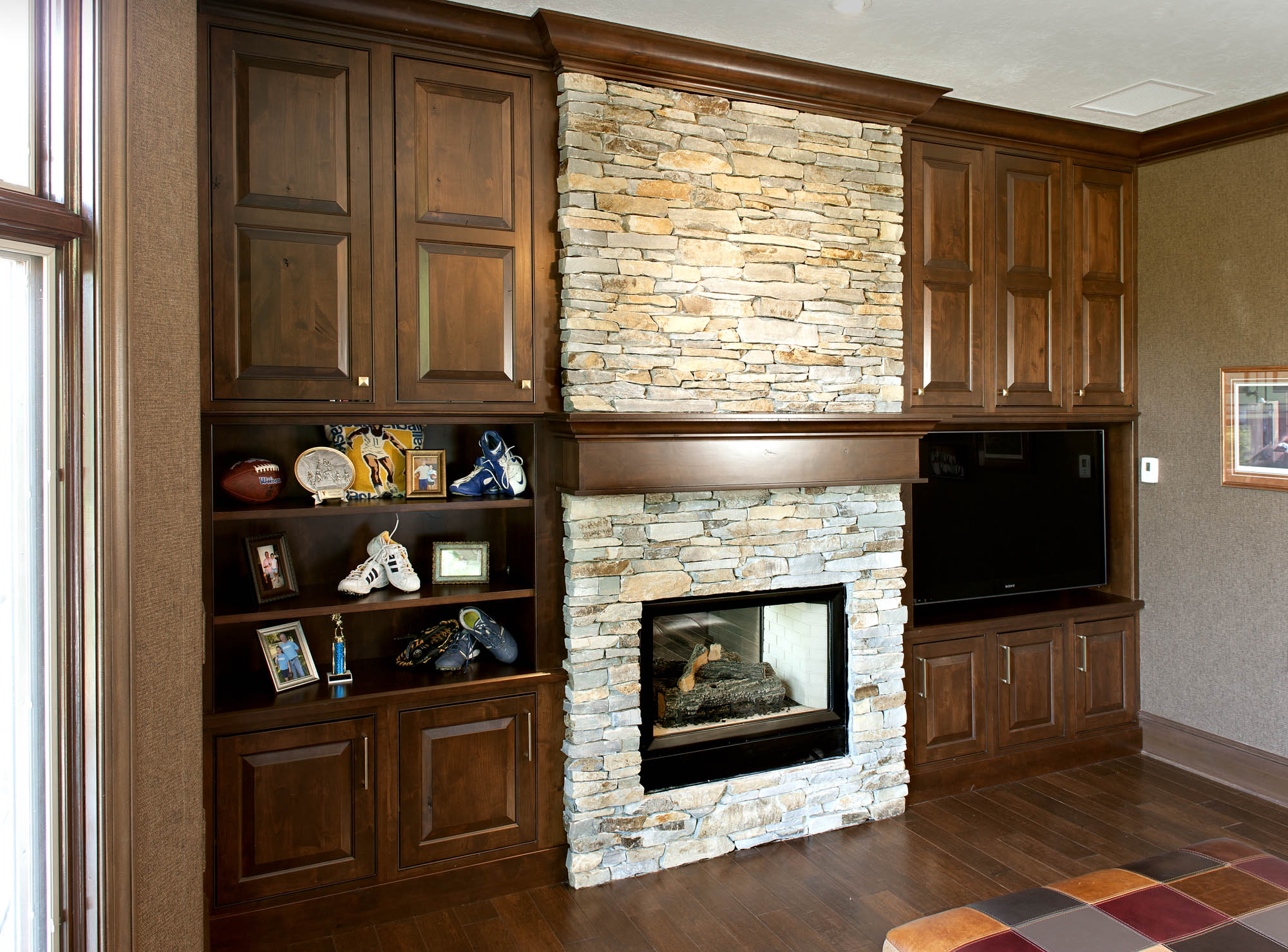 Stained home office fireplace surround in Distressed Coffee with Ebony Glaze by Showplace Cabinetry