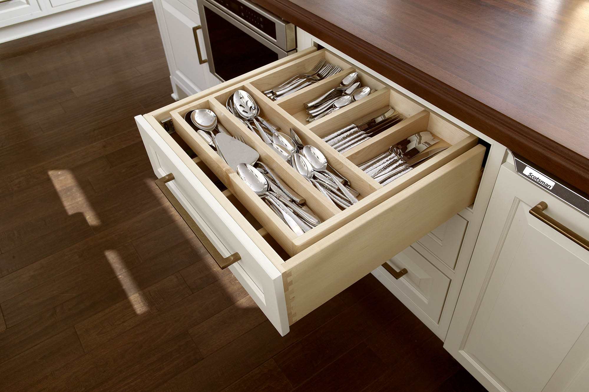 Painted kitchen island with cutlery drawer in Soft Cream by Showplace Cabinetry