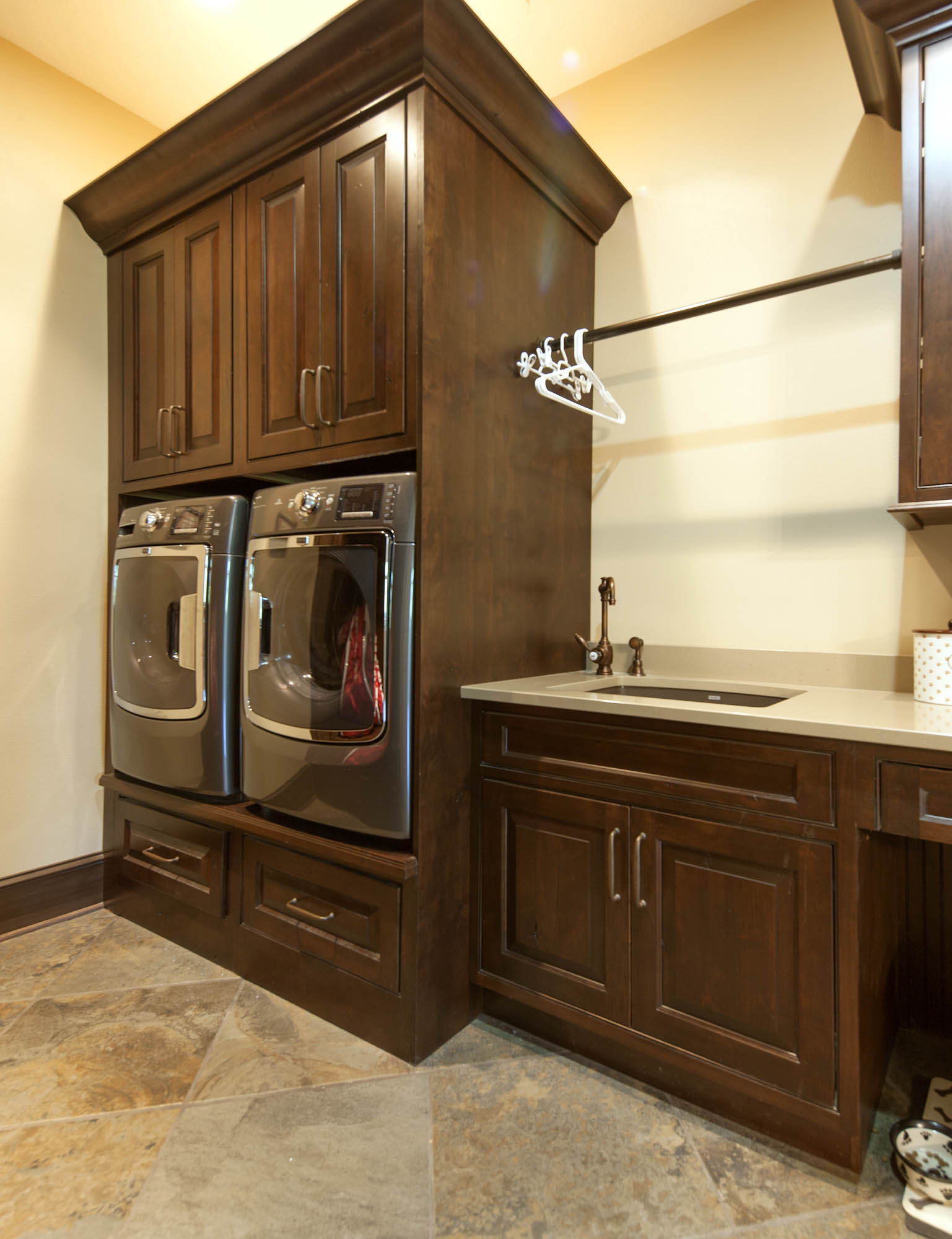 Stained laundry room cabinets in Distressed Coffee with Ebony Glaze by Showplace Cabinetry
