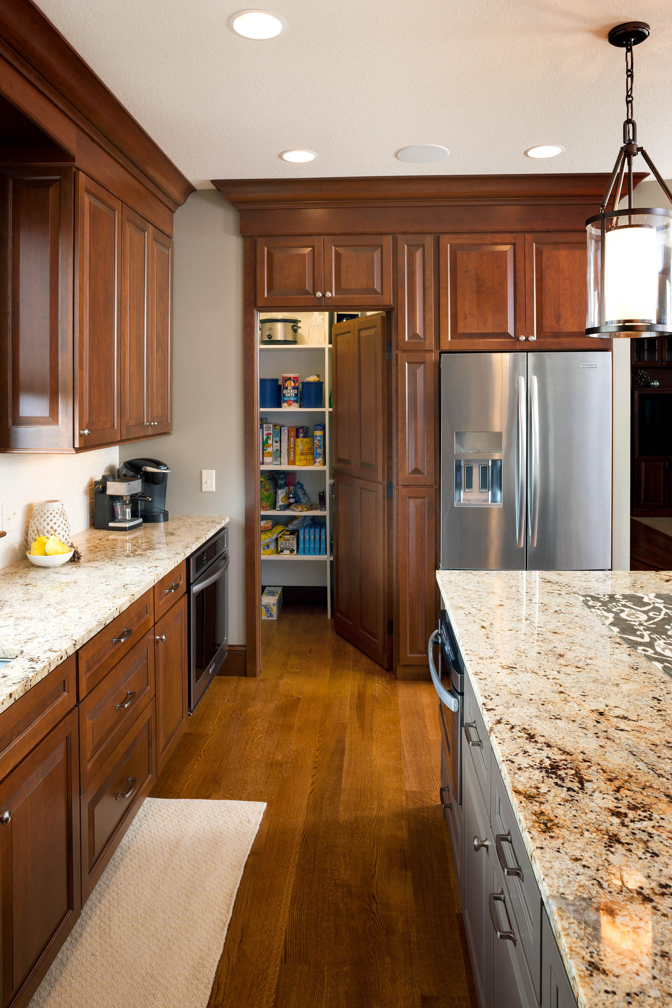 Stained kitchen pantry in Pecan with Ebony Glaze by Showplace Cabinetry