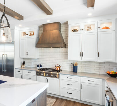A large painted kitchen with island utilizes paint grade species; the perimeter is painted Heron Plume and the wood hood is rustic alder stained Driftwood by Showplace Cabinetry.